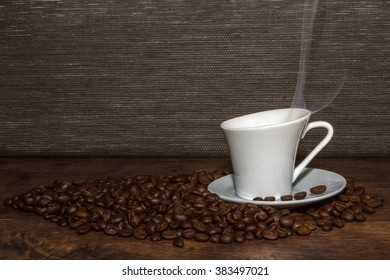 Hot aromatic coffee with black beans on wooden table