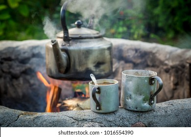 Hot and aromatic coffee with kettle on campfire