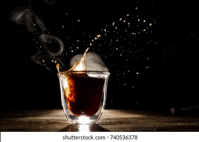 Hot and aromatic coffee spilling from glass cup located on the wooden table on the dark background