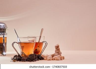Thé aromatique chaud sur fond rose. Théâtre en verre. Pile de sucre brun et de perfusion. Copier l'espace. Concept de cérémonie du thé