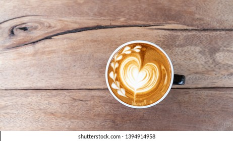 Hot art coffee cappuccino in a cup on wooden table background  with copy space
