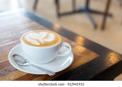 Hot art Latte Coffee in a cup on wooden table.