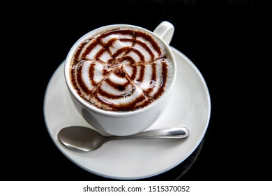Hot art Mocha Coffee in a cup on black table. Image on top view.