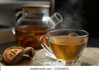 Hot bael fruit herbal tea poured into transparent cup with hot steam. Bael fruit herbal tea made of dried bael / quince fruit & boiled in clear teapot. Healthy beverage & hot herbal drink concept.