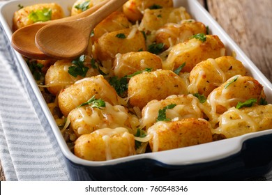 Hot Baked Tater Tots with cheese, meat, corn and parsley close-up in a baking dish on the table. horizontal