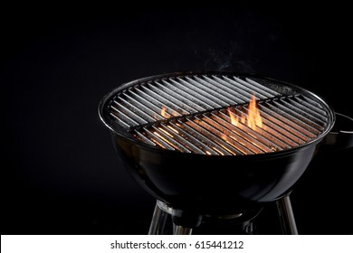 Hot barbecue fire with glowing coals ready to cook for an outdoor evening summer BBQ in a close up view of the round portable grill