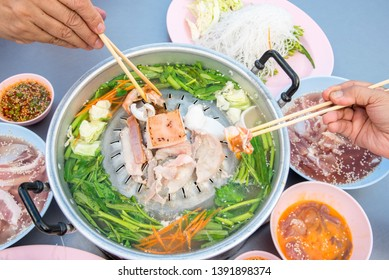 Hot barbecue Grill Pork on hot pan buffet, It's traditional Thai style BBQ, barbecue buffet pig pan and vegetables in soup, Cooking barbecue pork Fatty foods,