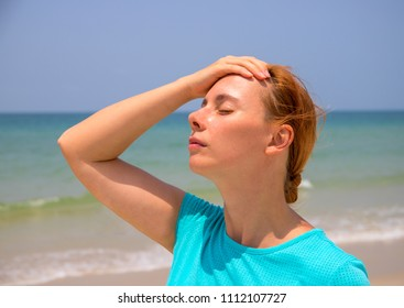 Hot beach and young woman. Woman on hot beach with sunstroke. Health problem on holiday. Medicine on vacation. Dangerous sun. Beach life. Sunstroke on sunny beach. Healthcare in tropics