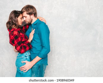 Hot beautiful woman and her handsome boyfriend. Models posing near gray wall in jeans clothes. Young passionate couple hugging before having sex. Sensual pair getting closer for kiss. Lover couple