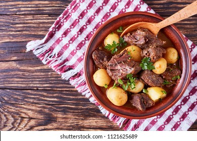 hot Beef Stew with tender cubes of meat, whole new potatoes, onion and herbs in a clay bowl on old rustic wooden table with napkin, irish cuisine, horizontal view from above, flatlay