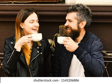 Hot beverage and lunch time concept. Woman and man with happy faces have date at cafe. Couple in love drinks espresso during coffee break. Girl and bearded guy have coffee on brown terrace background