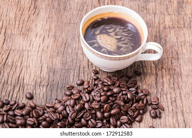 Hot black coffee in coffee cup and roasted coffee beans on wooden table
