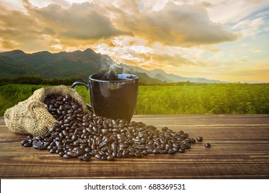 Hot black coffee cup and smoke with coffee beans on the dark wooden, cannabis and mountain background. Natural coffee concept