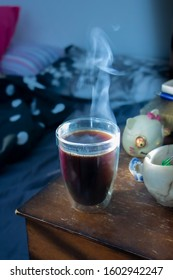 Hot black coffee cup with steam on bedside