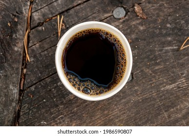 Hot black coffee on a camp log table top down view