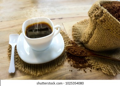 hot black coffee and coffee powder in sack on wooden floor