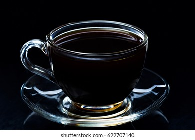 Hot black coffee smokes in a glass cup on a black background, studio light