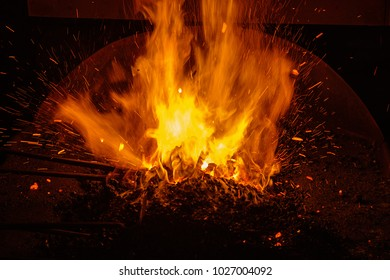 hot blacksmith forge with burning coals and sparks