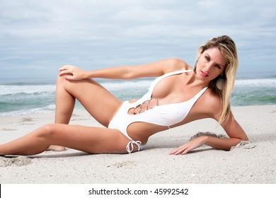 Hot blond in a white bikini having a good time on the beach.