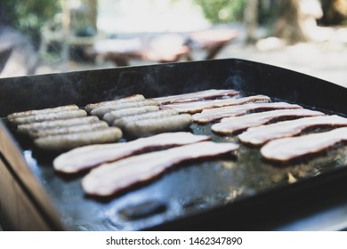Hot breakfast on a flat grill outside featuring bacon and sausage