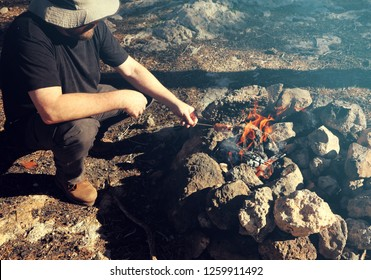 Hot bright bonfire at stones on sunny day. Burning logs. Glow flame. Man fries ( smokes) sausages on sticks at fire. Mountain forest picnic