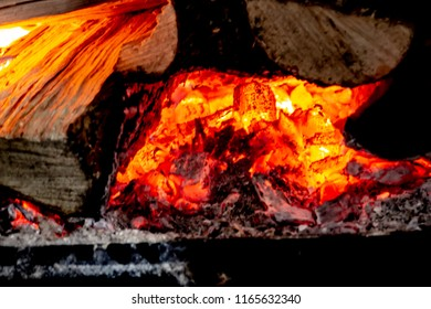 Hot burning embers in a wood stove. The embers are glowing orange, red and yellow.  The logs around the embers are visible.