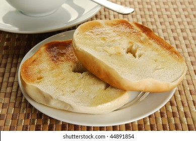 Hot buttered toasted bagels by a cup of coffee