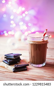Hot cacao drink in the glass on wooden table with chocolate bar. Multicolor lighting bokeh and glass holiday balls background.