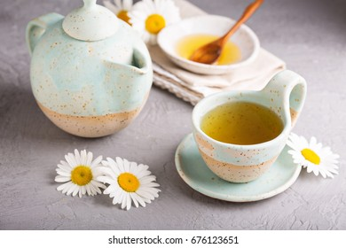 Hot camomille tea with honey in handmade ceramic cup