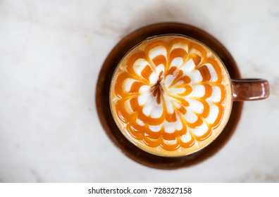 Hot cappucchino coffee with caramel on top in brown ceramic cup on marble desk , there is japanese cheese cake beside