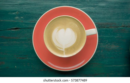 Hot cappuccino with beautiful latte art on wooden table