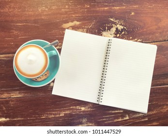 Hot cappuccino coffee with brown bread and notebook on the wooden background or texture