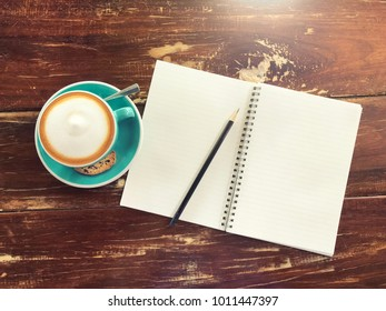 Hot cappuccino coffee with notebook and pencil on the wooden background or texture, copy space