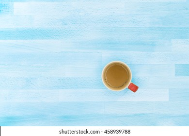 Hot Cappuccino Coffee Red Mug on Light Blue Wood Texture Office Table or Desk from Top View / Relax Moments / Business Template Artworks Design for Presentation Copy Space on Left