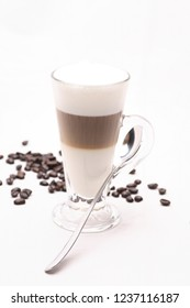 Hot Cappuccino  coffy in a clear glass on a white background with coffee beans.