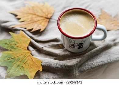 A hot cappuccino cup with colorful maple leafs