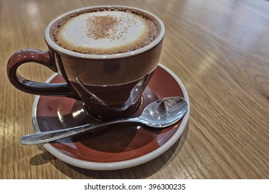 Hot cappuccino with high contrast effect in a mug on wooden table