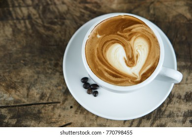 Hot cappuccino or latte art. A cup of coffee on the wooden table with roasted beans. Morning breakfast.The hearts shape created by pouring steamed milk.
