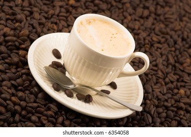 Hot cappuccino on coffee grains