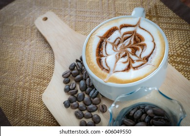 Hot cappucino art coffee on wooden texture table