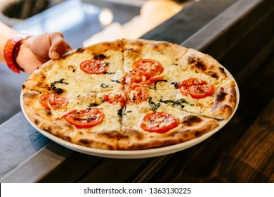 Hot Caprese Bianca Pizza from oven. Ingredients are Mozzarella, Parmesan, Olive oil, sliced tomato and Dough.