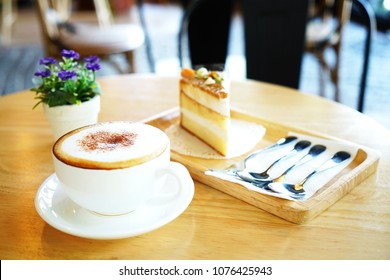 Hot capuchino coffee with caramel cake too soft and blurry on the wood table  violet flower;  stainless spoon set;relaxing and refreshing time.