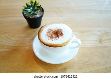 Hot capuchino coffee too soft and blurry plant background on wood table