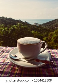 Hot capuchino coffee white cup spoon on table blue ocean view