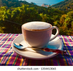 Hot capuchino coffee white cup spoon on table blue ocean green forest view