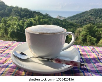 Hot capuchino coffee white cup spoon sea sky clouds view