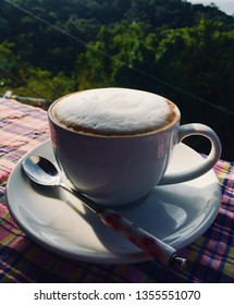 Hot capuchino coffee white cup spoon sunshine green view