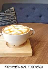 Hot caramel macchiato served in white cup on wooden saucer at cafe with cozy sofa and backrest pillow; shoot from mobile camera.