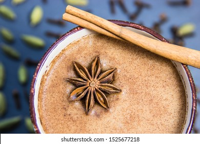 Hot Chai Tea In Mug With Star Anise & Cinnamon Bark & More Ingredients In Background Including Green Cardamon & Whole Cloves