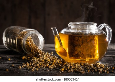 Hot Chamomile Tea in a clear Teapot and Dried Flowers on a Wood Table